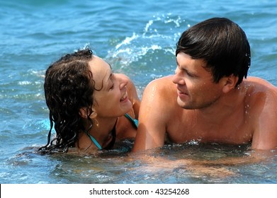 Happy young woman and man in water
