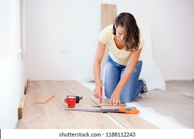 Happy young woman measuring and marking laminate floor tile. Installing laminate flooring in new apartment. Cup of coffee and tools on the floor. Home improvement and renovation concept