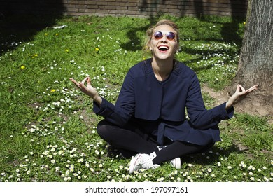 Happy young woman meditating on grass, United Kingdom