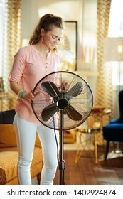 happy young woman at modern home in sunny hot summer day swtitching on metallic floor standing fan.
