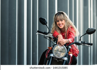 happy young woman mounting on a red motorbike