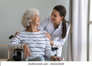 Happy young woman nurse help disabled paralyzed senior grandma patient sit on wheelchair at home hospital, female carer provide old handicapped lady medical service, elder people healthcare concept