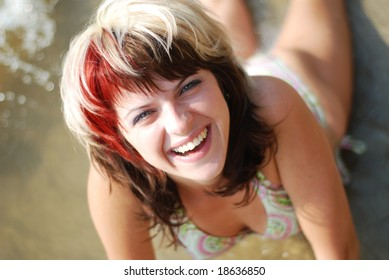Happy young woman on the beach of the river