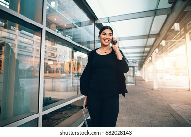 Happy young woman on business trip walking with luggage and talking on cellphone at airport. Travelling businesswoman making phone call.