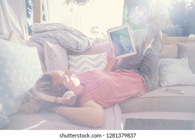 Happy young woman on outdoor sofa relaxing and using digital tablet, wearing headphones listening to music. People at home technology concept