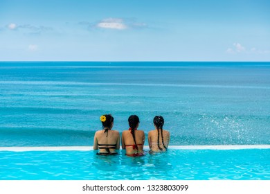 Happy young woman on summer beach holiday relaxing in luxury spa resort in infinity swimming pool with sea view. Healthy lifestyle, family travel background.