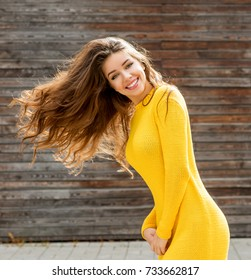 Happy young woman on sunny autumn day. Outdoor lifestyle photo. Brown hair. Warm autumn. Beautiful fall day.