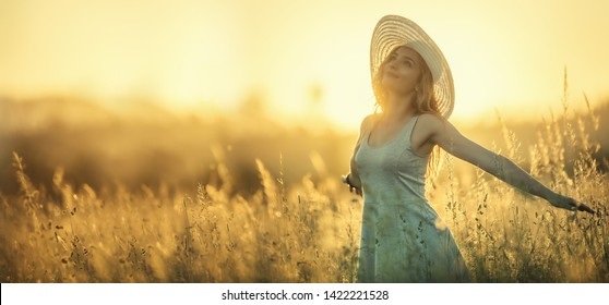 Happy young woman on the sunset or sunrise in summer nature with open hands.