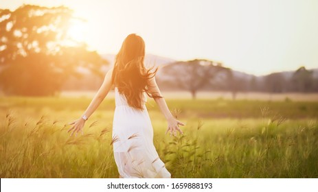 Happy young woman on the sunset or sunrise in summer nature