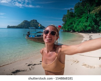 Happy young woman on tropical beach in Thailand taking selfie picture with traditional long tail boat and limestone Islands; Girl on vacation enjoying idyllic white sand beaches