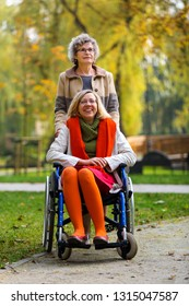 happy young woman on wheelchair with old woman in the park in autumn