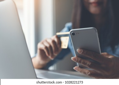 Happy young woman online shopping by credit card payment on mobile smart phone and laptop computer, internet banking, mobile banking, e commerce, e business, financial technology Fintech concept.