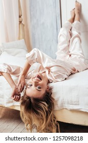 happy young woman in pajama sticking tongue out and looking at camera in bed at home