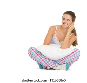 Happy young woman in pajamas sitting with pillow