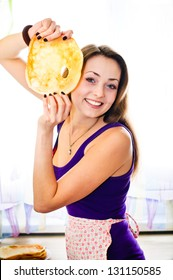 happy young woman with pancake at the kitchen smiling