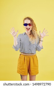 Happy young woman in paper 3D glasses shouting from excitiment, isolated on yellow background