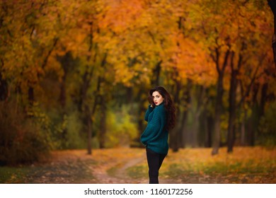 Happy young woman in park on sunny autumn day. Cheerful beautiful girl in green sweater outdoors among yellow leaves on beautiful fall day