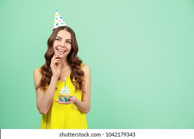 Happy young woman in party hat holding birthday cupcake with candle on color background