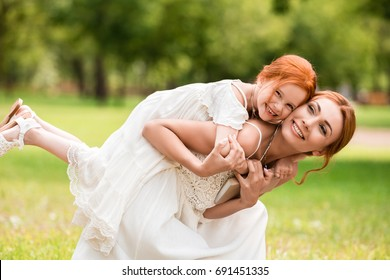 happy young woman piggybacking adorable little daughter at park