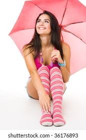 Happy young woman in pink sitting with umbrella isolated on white