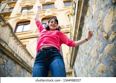 Happy young woman in pink sweater listening to music and dancing in the street. Low angle view
