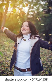 Happy young woman playing with autumn leaves in colorful woodland tossing them in the air with a joyful smile in the glow of the sun