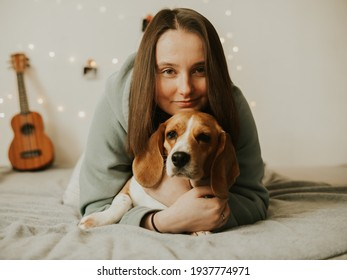 Happy young woman playing with her dog on a white background. Beagle dog with owner. Girl and dog at home. Beautiful girl having fun with beagle dog at home on a bed.