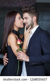 Happy young woman playing on boyfriends face on dating indoors