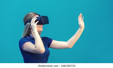 Happy young woman playing on VR glasses indoor – Virtual reality concept with young girl having fun with headset goggles touching air during VR experience – Digital generation trend