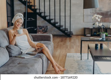 Happy young woman poses wrapped in bath towel, drinks aromatic coffee and reads magazine, sits on comfortable sofa, poses in living room at home. Domestic atmoshpere, leisure time, lifestyle