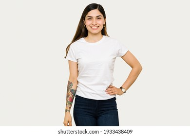 Happy young woman posing with one hand on her hip and smiling. Woman wearing a mock up t-shirt design while standing in front of a white background