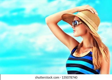 Happy young woman posing over blue sky.