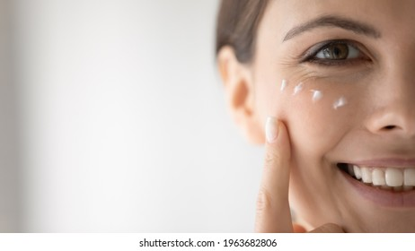 Happy young woman putting moisturizing nourishing cream, cleansing lotion on smiling face, applying cosmetics for keeping healthy fresh skin. Cosmetology, skincare concept, Close up, cropped portrait