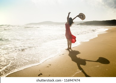 Happy young woman raises her arms towards the sea