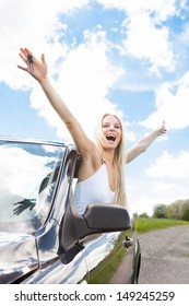 Happy Young Woman Raising Hand Out Of Car Window