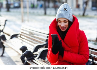 Happy young woman read message and look at the mobile phone aka smartphone and wonder. Wearing red down jacket, black, touch friendly gloves and knitted hat. Winter holiday, communication concept