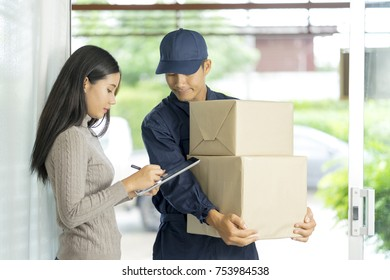 Happy young woman receive boxes, shipment, parcel from delivery man and sign on receiver note. Shipping Man holding many boxes in hand and waiting receiver to complete signature. Delivery concept.
