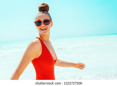 happy young woman in red beachwear on the beach walking