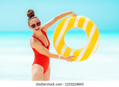 happy young woman in red beachwear on the beach showing yellow inflatable lifebuoy