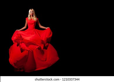 Happy young woman in a red dress in full growth. Black background. party or a carnival, a long red dress. beautiful model with makeup and styling, red lips