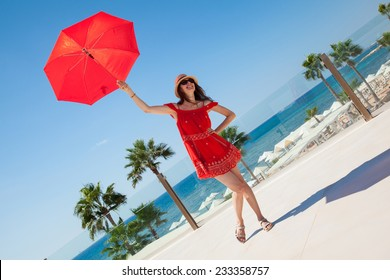 Happy young woman in a red dress with a red umbrella on seafront background