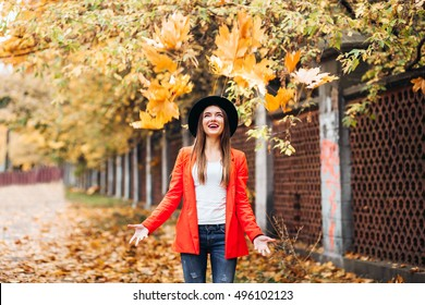 Happy young woman in red jacket and black hat throwing leaves and smiling on colorful nature city background, autumn