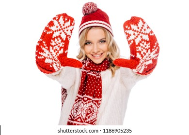 happy young woman in red mittens smiling at camera isolated on white