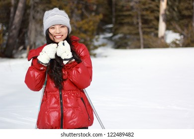 A happy young woman in red in the snow