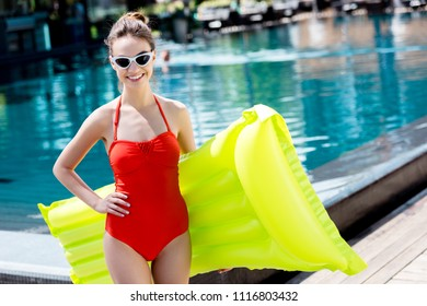 happy young woman in red swimsuit with inflatable mattress standing at poolside