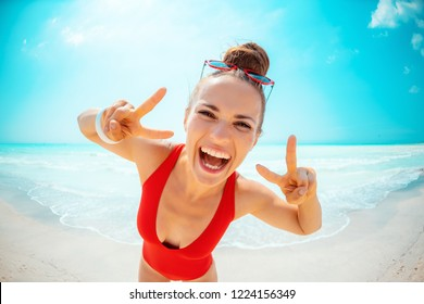 happy young woman in red swimwear on the beach showing victory gesture