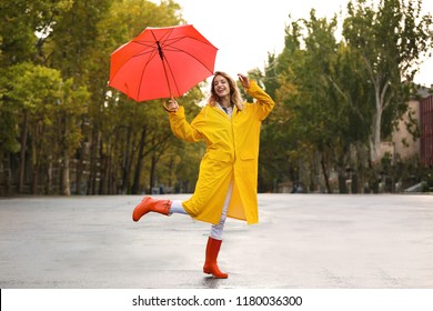 Happy young woman with red umbrella wearing yellow raincoat on street