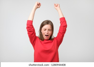 Happy young woman in red wear gesturing and keeping eyes closed