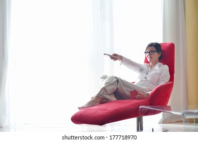happy young woman relax at home on sofa in bright living room and watching tv