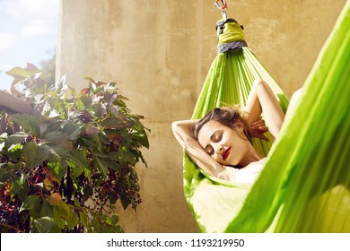 happy young woman relaxed lies in a hammock on the balcony House. Woman basks and sunbathes in a hammock
